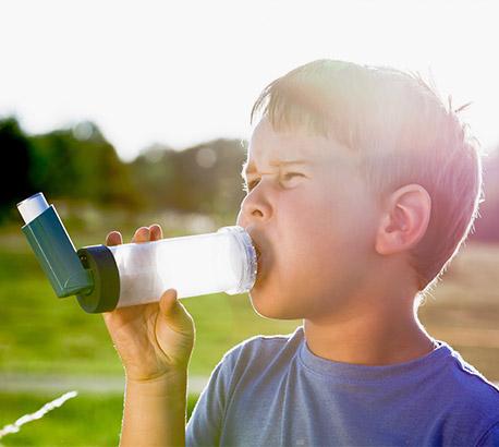 Asthmatic boy using a puffer
