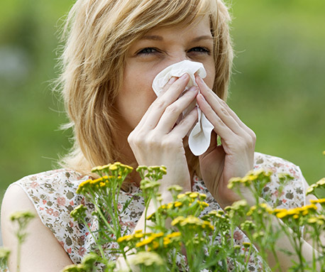 Woman with hayfever sneezing
